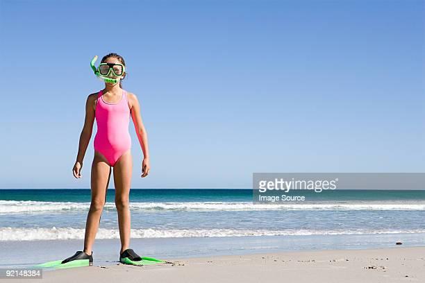 Giovane ragazza in piedi sulla spiaggia in pinne e maschera per lo snorkeling