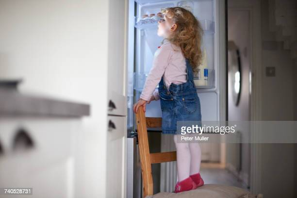 Young girl standing on chair, looking into fridge