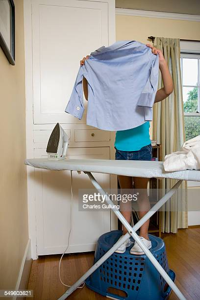 Young Girl Standing on Laundry Basket While Ironing