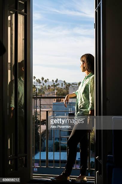 Young girl standing on open balcony, Santa Monica, California