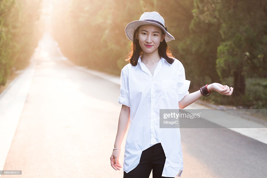 Young Girl Standing on Road in Sunset Glow : Stock Photo