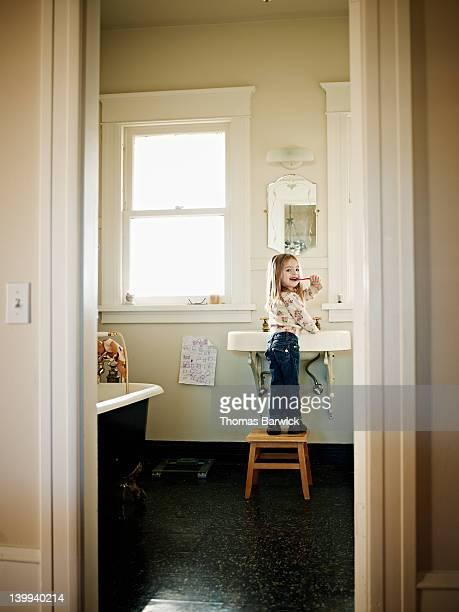 Young girl standing on stool brushing teeth