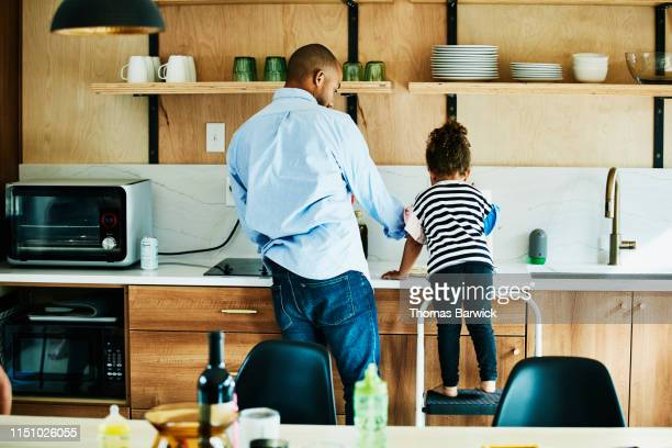 young girl standing on stool in kitchen while helping father make dinner - black man bulge stock pictures, royalty-free photos & images
