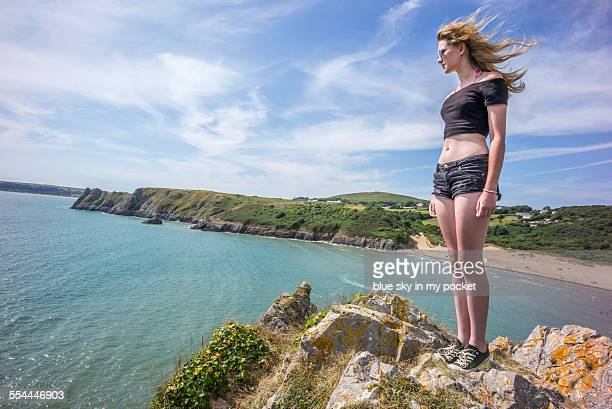 Young girl standing on the top of a cliff