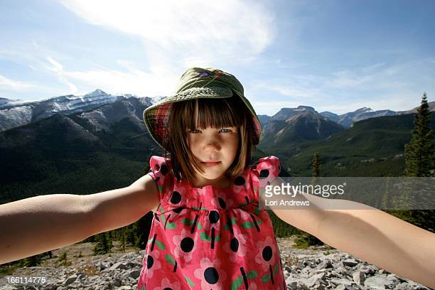 Young girl standing on top of a mountain