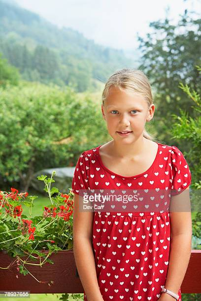 Young girl standing outdoors by flowerboxes.