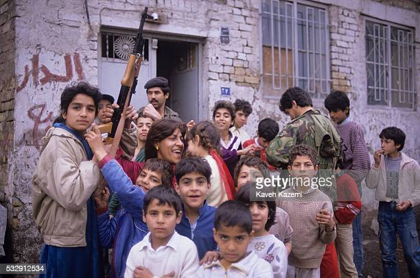 A young girl standing outside her home with her family cheers while holding an AK47 automatic assault rifle after Iraqi troops came back from Kuwait...