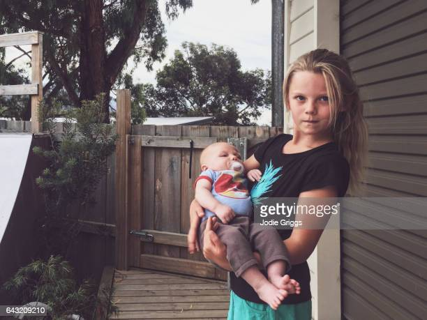 Young girl standing outside holding baby brother