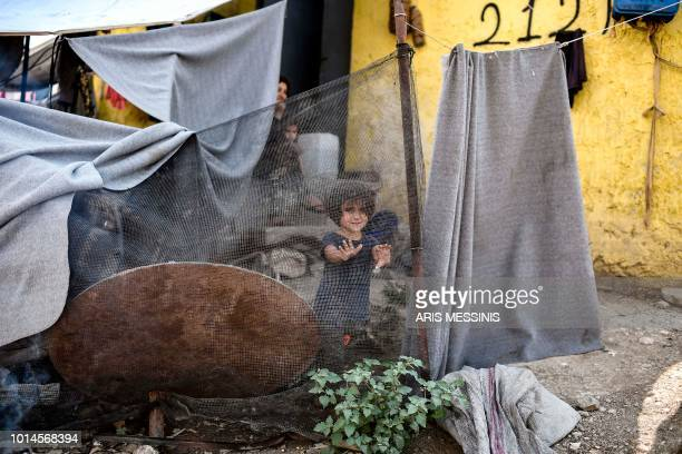 A young girl stands at a camp next to the Moria refugee camp in the island of Lesbos on August 5 2018