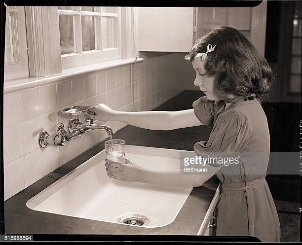A young girl stands at a sink filling a glass with water Undated photograph circa 1950's