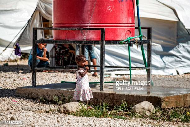Young girl stands by a water cistern at Camp Roj, housing family members of people accused to belong to the Islamic State group who were relocated...