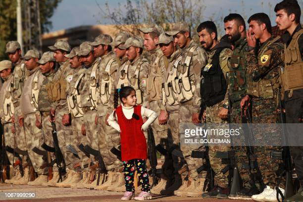 Young girl stands in front of fighters from the Syrian Democratic Forces as they attend the funeral a fellow fighter killed in the town of Hajin...