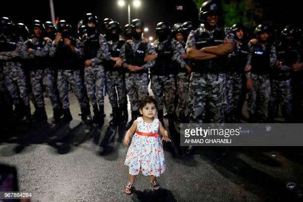 A young girl stands in front of Jordanian antiriot police during a protest near the prime minister's office in Amman Jordan on June 5 2018 Jordanian...