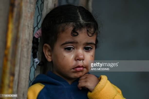 TOPSHOT A young girl stands inside a tent at a makeshift camp next to the camp of Moria in the island of Lesbos on November 30 2019 Conditions remain...