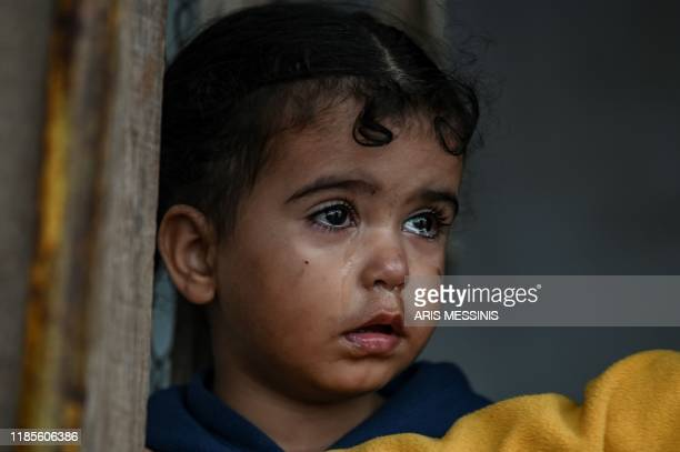 A young girl stands inside a tent at a makeshift camp next to the camp of Moria in the island of Lesbos on November 30 2019 Conditions remain...