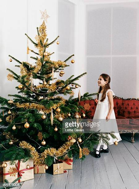 Young Girl Stands Next to a Decorated Christmas Tree in Her Living Room, Looking Up at it in Awe