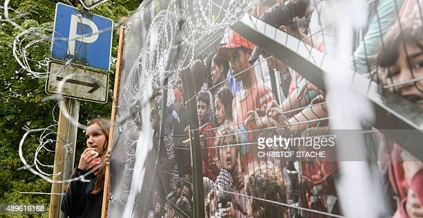 A young girl stands next to a picture of refugees behind a barbed wired fence and blows a whistle as she protests against the visit of the Hungarian...