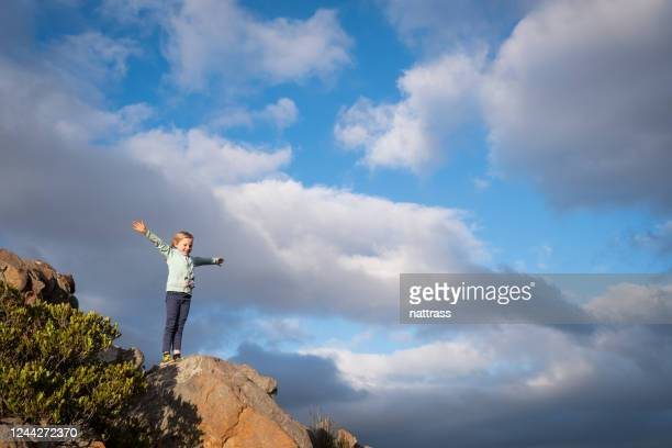 young girl stands on a rock with arms outstretched - overberg stock pictures, royalty-free photos & images