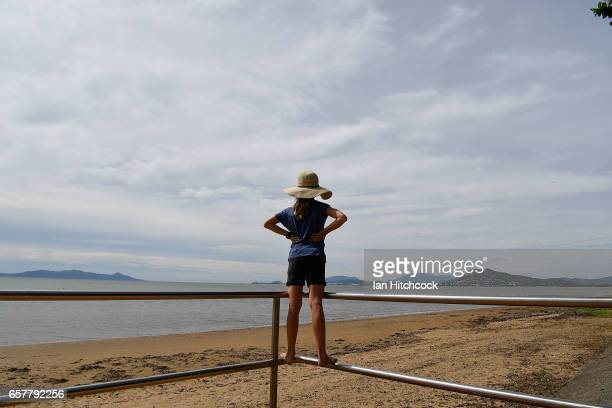 A young girl stands on railings looking out to sea as residents prepare and wait for Cyclone Debbie on March 26 2017 in Townsville Australia Cyclone...