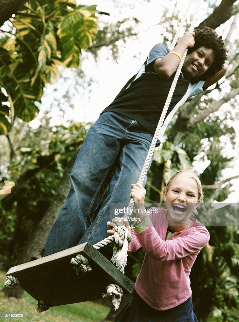 Young Girl Stands on Top of a Swing in a Garden, Being Pushed by Her Friend : Stock Photo