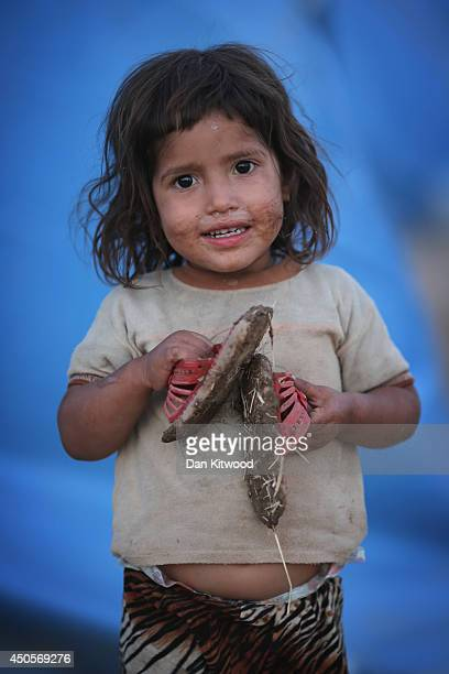 Young girl stands outside her tent at a temporary displacement camp set up next to a Kurdish checkpoint on June 13, 2014 in Kalak, Iraq. Thousands of...