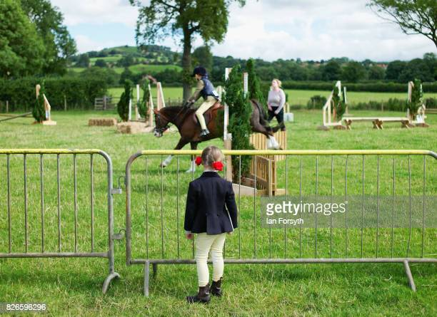 Young girl stands watching a show jumping event during the Osmotherley Country Show on August 5, 2017 in Osmotherley, England. The annual show hosts...