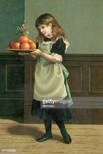 A young girl stands with a plate of oranges topped with a sprig of hollyberry during her preparation for the Christmas Season Undated color...