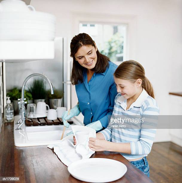 young girl stands with her mother at the kitchen sink, helping her to wash up and dry the pots - kids with cleaning rubber gloves stock pictures, royalty-free photos & images