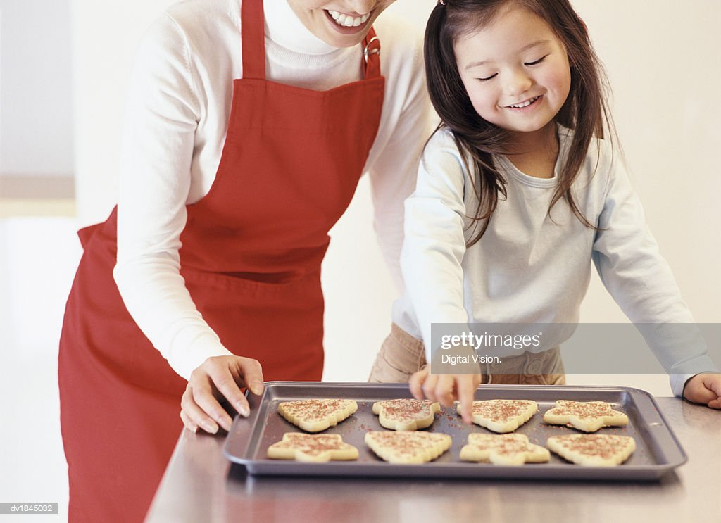 Young Girl Stands With Her Mum by the Kitchen Counter, Choosing a Christmas Cookie From a Baking Tray : Stock Photo
