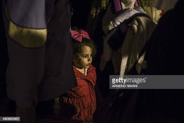 A young girl stands with other migrants and refugees waiting to board a train near the registration camp after crossing the GreekMacedonian border...