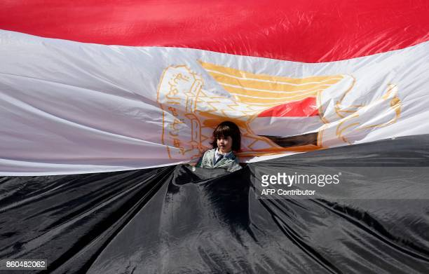 TOPSHOT A young girl stands wrapped in an Egyptian flag as Palestinians gather in Gaza City to celebrate after rival Palestinian factions Hamas and...