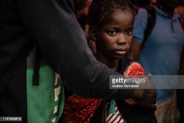 Young girl stares into the distance as people from the town of Buzi unload at Beira Port after being rescued on March 22, 2019 in Beira, Mozambique....