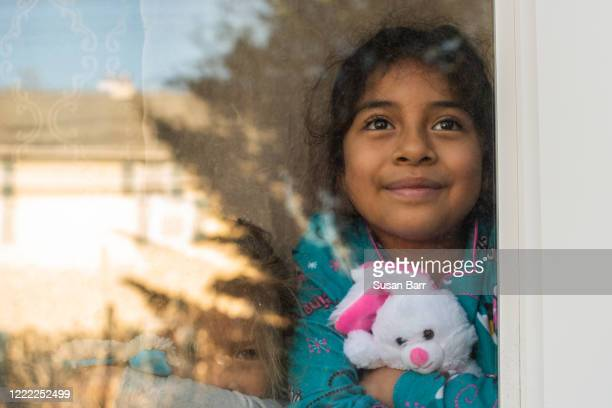 young girl stares out window with easter bunny