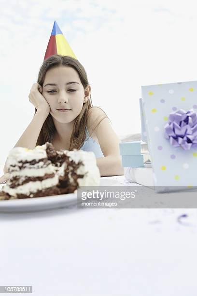 Young girl staring at birthday cake
