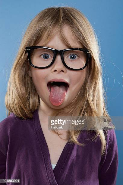 a young girl sticking out her tongue playfully, studio shot - little girl sticking out tongue stock photos and pictures