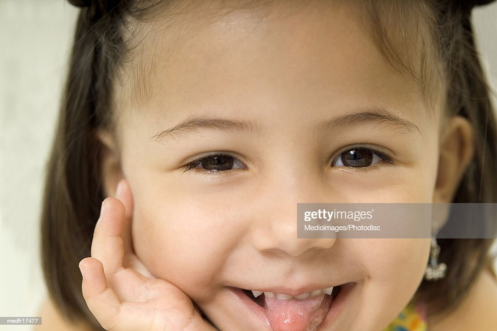 Young girl sticking out tongue : Stock Photo