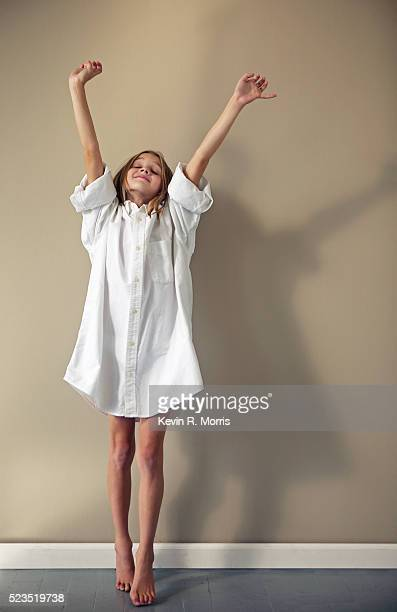 Young Girl Stretching in Men's Dress Shirt