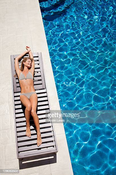 young girl stretching out next to pool