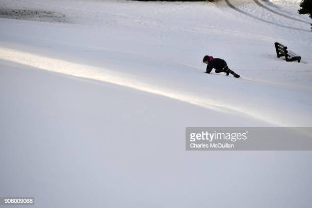 A young girl struggles to climb up a snow covered slope on January 17 2018 in Belfast Northern Ireland The Met Office has placed an amber weather...