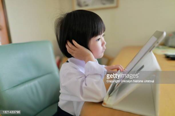 young girl student seriously looking at digital tablet - saitama prefecture stock pictures, royalty-free photos & images