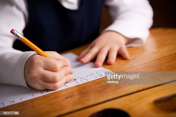 Young Girl Student Sitting in School Desk Writing the Alphabet