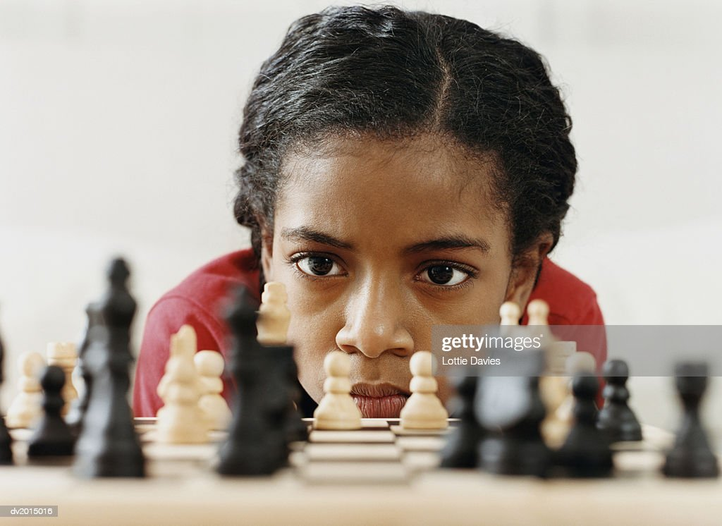 Young Girl Studying a Chess Board : Stock Photo