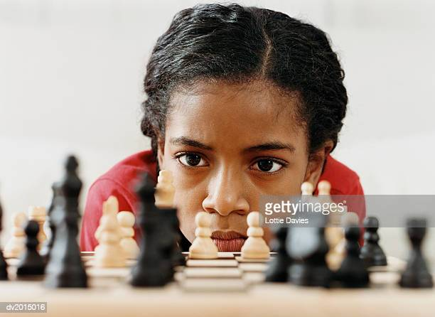 young girl studying a chess board - playing chess stock pictures, royalty-free photos & images