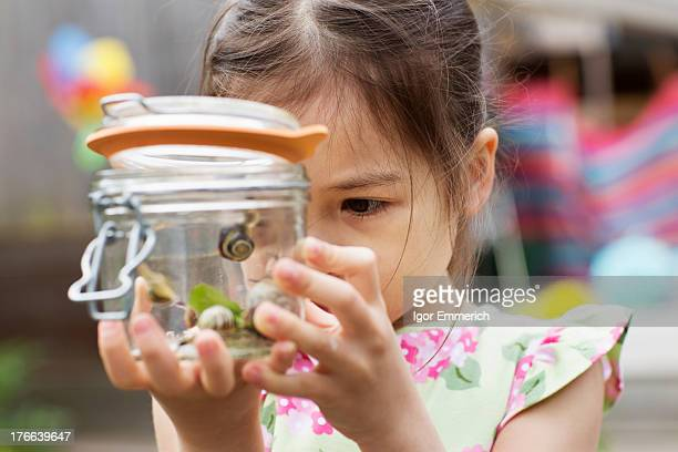 Young girl studying jar of snails