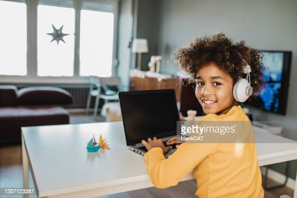 young girl studying with laptop at home - child stock pictures, royalty-free photos & images