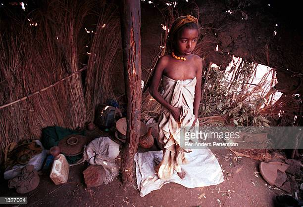 A young girl suffering from malaria stands in her family hut February 9 2001 in the Erer Valley in eastern Ethiopia Villagers in the Muslim area have...