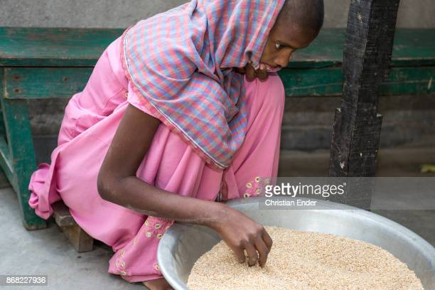 A young girl suffering tuberculosis is sitting in front of a big metal pot filled with dry rice putting the scarf in front of her mouth