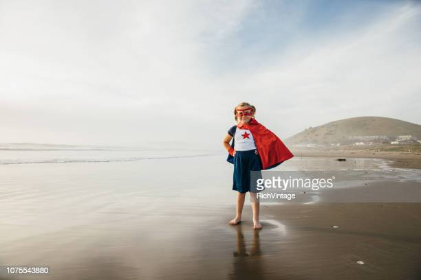 young girl superhero on california beach. - stereotypical stock pictures, royalty-free photos & images