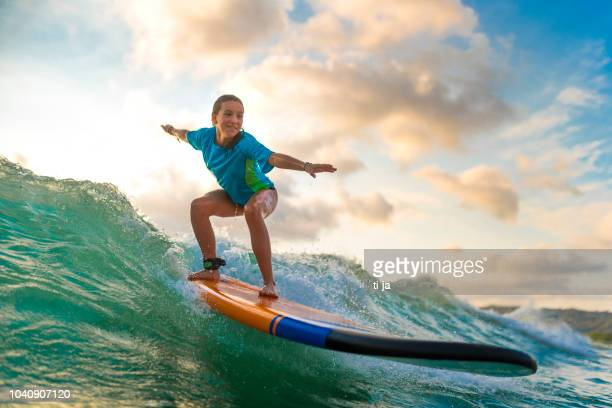 young girl surfing at sunset - surfboard stock pictures, royalty-free photos & images