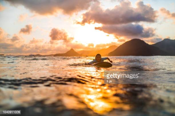chica joven surf al atardecer - lombok fotografías e imágenes de stock